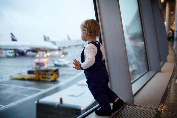 barn som tittar ut genom fönstret på en flygplats